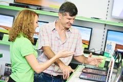 Comprador assistente da ajuda da mulher do vendedor que escolhe o laptop fotografia de stock