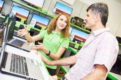 Comprador assistente da ajuda da mulher do vendedor que escolhe o portátil imagem de stock