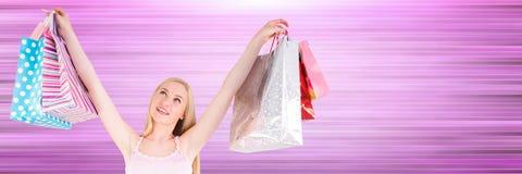 Comprador con los bolsos en aire contra fondo púrpura borroso Foto de archivo libre de regalías