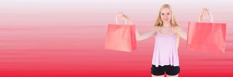 Comprador con los bolsos rojos contra fondo rojo borroso Fotos de archivo libres de regalías