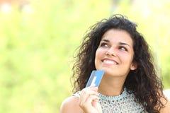 Comprador con una tarjeta de crédito que piensa qué comprar Imagenes de archivo