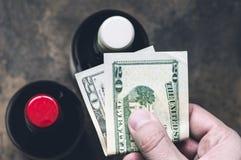 Comprador de la mano con los dólares en licorería Imagen de archivo libre de regalías