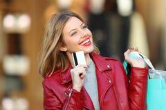 Comprador de la moda que piensa sosteniendo una tarjeta de crédito Foto de archivo