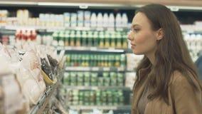 Comprador de la mujer en la sección de los dulces en el supermercado almacen de metraje de vídeo