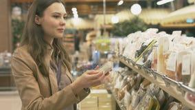 Comprador de la mujer en la sección de los dulces en el supermercado metrajes