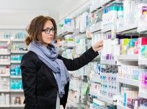 Comprador de sexo femenino que elige el producto en farmacia Imagen de archivo