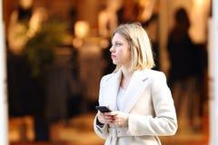 Comprador distraído que sostiene el teléfono en la calle Fotografía de archivo
