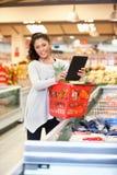 Comprador en almacén usando la tablilla digital fotografía de archivo