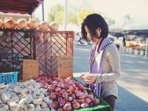 Comprador en el mercado al aire libre - chalotes, ajo Fotografía de archivo libre de regalías