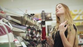 Comprador fêmea que guarda o ferro de ondulação vídeos de arquivo