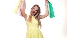 Comprador feliz de la mujer joven que sostiene los panieres en el fondo blanco en estudio almacen de video