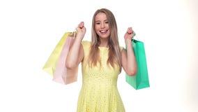 Comprador feliz de la mujer joven que sostiene los panieres en el fondo blanco en estudio metrajes