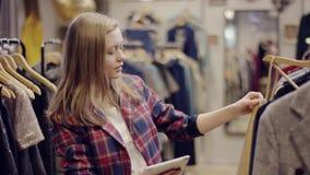 Comprador femenino adulto hermoso que usa la PC de la tableta mientras que elige la ropa en una tienda de ropa almacen de video