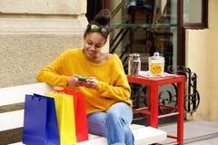 Comprador femenino al aire libre en banco usando el teléfono móvil Fotos de archivo