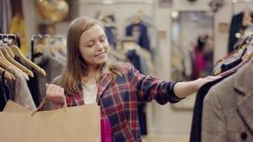 Comprador femenino bonito joven buscando la nueva ropa en una tienda de ropa que sostiene bolsos de compras almacen de video