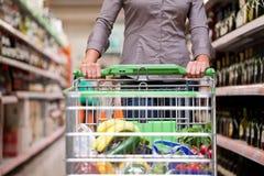 Comprador femenino con la carretilla en el supermercado Imagen de archivo
