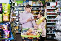 Comprador femenino con la hija adolescente que busca para las bebidas Imagenes de archivo