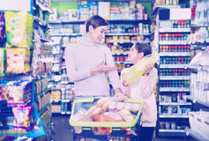 Comprador femenino con la hija adolescente que busca para las bebidas Imagen de archivo libre de regalías