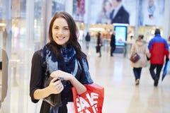 Comprador femenino con los bolsos de la venta en alameda de compras Foto de archivo