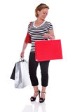 Comprador femenino con los panieres que comprueba su reloj aislado. Foto de archivo libre de regalías