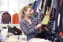 Comprador femenino en la tienda de descuento que mira los bolsos fotografía de archivo