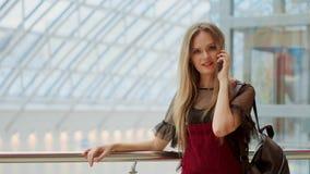 Comprador femenino feliz que habla en el teléfono y la sonrisa metrajes
