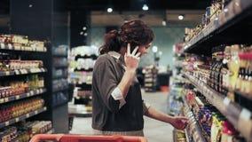 Comprador femenino hermoso que intenta elegir productos en el colmado mientras que habla con alguien en el teléfono metrajes