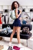 Comprador femenino hermoso que se coloca que mira detrás la cámara en las zapatillas de deporte que llevan de la nueva del vestid Imagenes de archivo