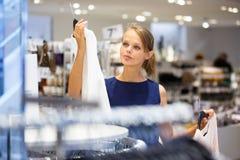 Comprador femenino joven hermoso en una tienda de ropa Imagen de archivo libre de regalías