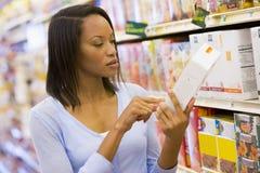Comprador femenino que controla el etiquetado de alimentos fotografía de archivo libre de regalías