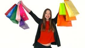 Comprador femenino que sostiene los panieres multicolores en el fondo blanco en estudio Deje el ` s ir concepto que hace compras almacen de metraje de vídeo