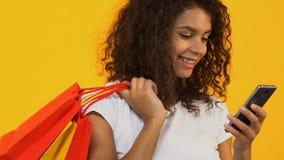 Comprador femenino sonriente con los bolsos de compras usando el smartphone, compra en línea, app almacen de video