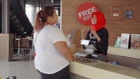 Comprador gordo que pide los alimentos de preparación rápida en café almacen de metraje de vídeo