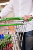 Comprador masculino con la carretilla en el supermercado Imágenes de archivo libres de regalías