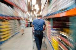 Comprador masculino en tienda con el carro de la compra Fotos de archivo libres de regalías