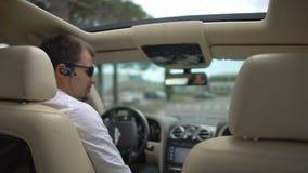 Comprador masculino que prueba el nuevo automóvil costoso en los caminos de ciudad, prueba de conducción metrajes
