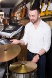 Comprador masculino que selecciona los tambores y los accesorios Fotos de archivo libres de regalías