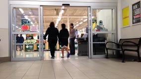 Comprador que camina a través de la entrada principal almacen de metraje de vídeo