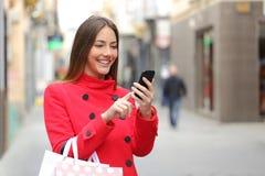 Comprador que compra en línea en el teléfono elegante Imagenes de archivo