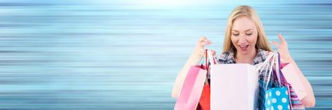 Comprador que mira en bolsos contra fondo azul borroso Fotografía de archivo libre de regalías