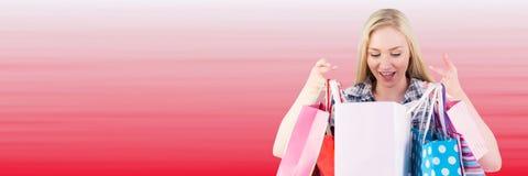 Comprador que mira en bolsos contra fondo rojo borroso Fotografía de archivo libre de regalías