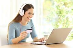 Comprador que paga en la línea música con la tarjeta de crédito Imágenes de archivo libres de regalías