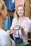 Comprador que paga mercancías usando la máquina de la tarjeta de crédito Imágenes de archivo libres de regalías