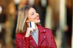 Comprador que se pregunta qué comprar sostener una tarjeta de crédito Imágenes de archivo libres de regalías