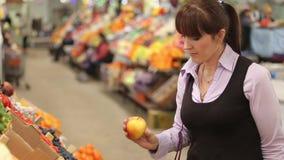 Comprador que selecciona la fruta en el mercado del granjero metrajes