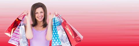 Comprador que soporta bolsos contra fondo rojo borroso Fotos de archivo