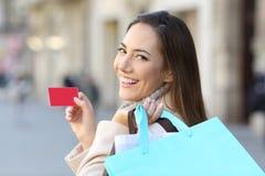 Comprador que sostiene los panieres y la tarjeta de crédito Foto de archivo