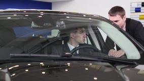 Comprador que tem a conversação com o vendedor do carro durante a inspeção do carro video estoque