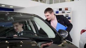 Comprador que tem a conversação com o vendedor do carro durante a inspeção do carro filme