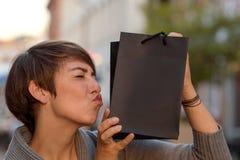 Comprador satisfecho que besa su bolso del boutique Imagenes de archivo